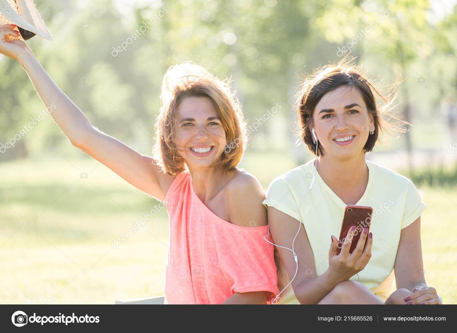 be6981fc87a5 Dos Chicas Guapas Risueños Sentados Césped Escucha Música Smartphone ...