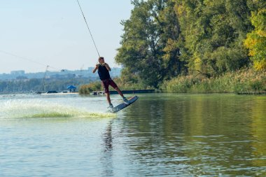Wakeboarder is flying behind the cable among the spray during a training in the cable park.