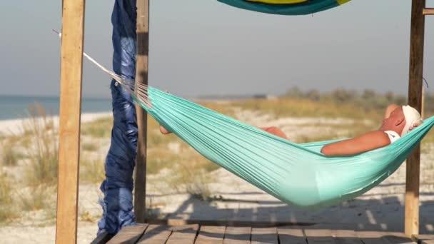 Man ellazítja a függőágy bungalow veranda, a hátteret a türkizkék tenger. Csodálatos napos a strandon.