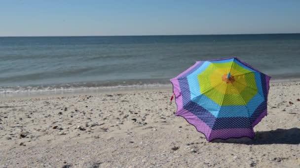 Wind trägt an einem sonnigen Tag einen bunten Regenschirm am Strand entlang.