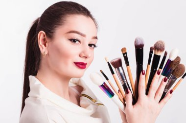 The face of a beautiful girl and make-up brush on white backgrou