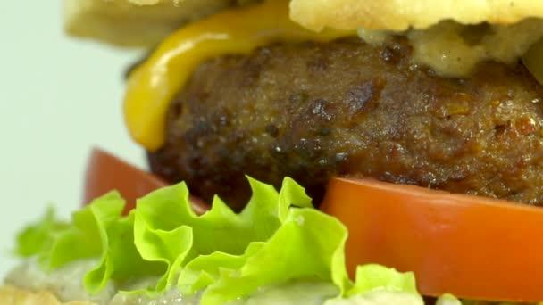 Cheeseburger s lilku omáčka, hovězí maso, sýr čedar, hlávkovým salátem, rajčaty a okurky. Makro snímek zblízka