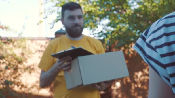 The postman delivers a parcel for a young woman
