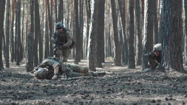 Slow-motion shooting as a soldier pulls a wounded comrade from under fire