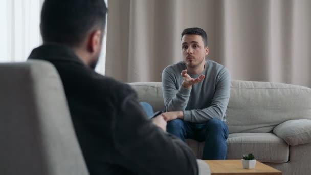 muž seděl na pohovce, mluvil s jeho terapeut.