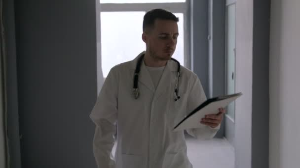 Doctor with paper goes on dark corridors