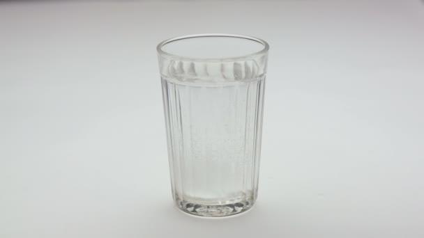 Aspirin nebo šumivá pilulka kapající do sklenice vody.