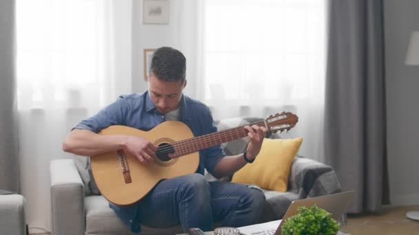 Pohledný muž, který hraje na pohovce na akustickou kytaru