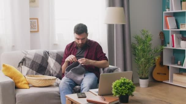 Panování člověka sedícího na pohovce a sledování pletací výukového programu na přenosném počítači