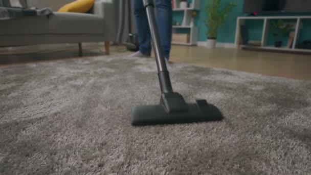 Mann reinigt Teppich mit Staubsauger