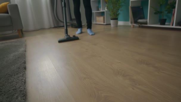 Handheld-Aufnahme einer jungen schönen Frau, die ihr gemütliches Wohnzimmer saugt