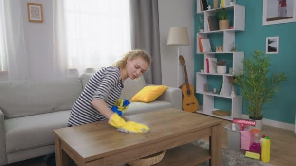 Handschuss einer jungen Frau wischt Couchtisch mit Lappen ab