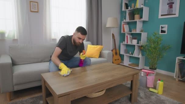 Muž na kávovém stole v útulném obývacím pokoji peče prach.
