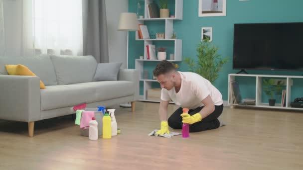 Vergrößern Junger Mann räumt nach Umzug in neue Wohnung auf.