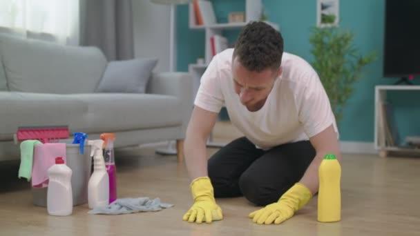 Umkippen des Mannes fühlt sich müde, wenn er nach dem Putzen im Wohnzimmer auf dem Boden sitzt