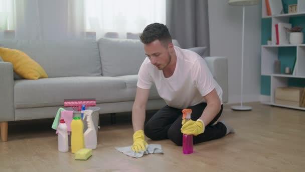 Člověk se cítí unavený sedět na dřevěné podlaze v obývacím pokoji po vyčištění doma