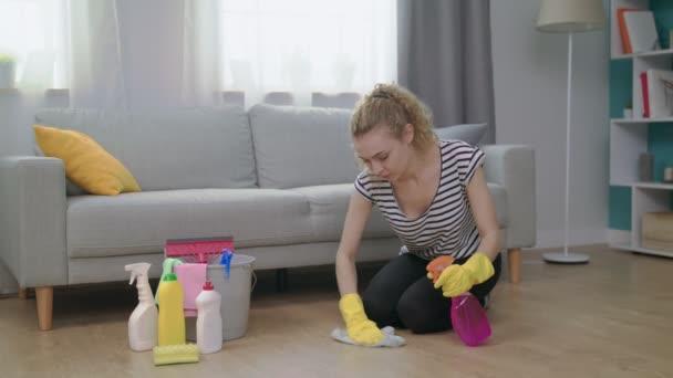 Mladá žena ve žlutých rukavicích s látkou čištění podlahy doma v obývacím pokoji