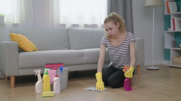 eine müde Frau massiert ihre Schulter beim Putzen des Wohnzimmers