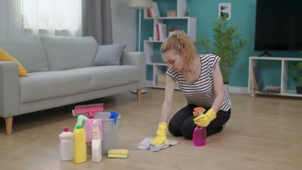 Panování ženy ve žlutých rukavicích s látkou na čištění látky v obývacím pokoji
