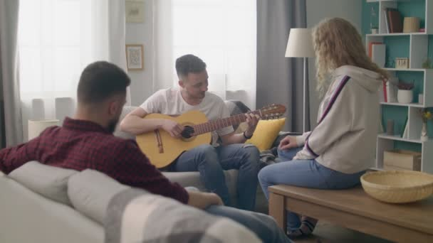 Handheld shot of young man plays guitar for his friends in a cozy living room.