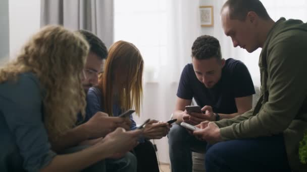 A group of friends use smartphones in the living room