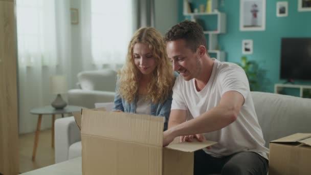 glückliches Paar sitzt auf Couch im Wohnzimmer offen Auspacken Pappkartonpaket