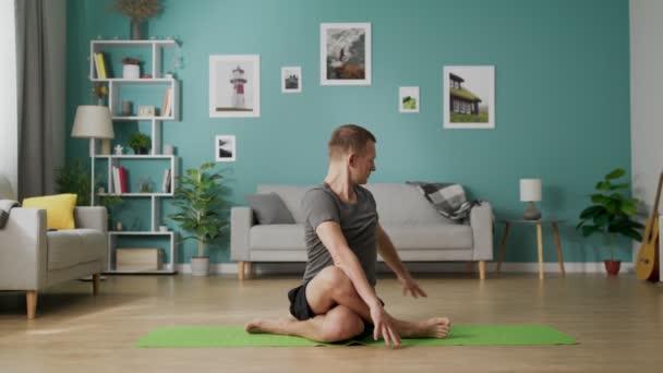 Fiatal alkalmas ember, az emeleten a nappali csinál különböző jóga pózok
