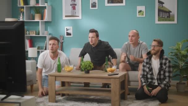 Vier männliche Freunde sitzen auf der Couch und beobachten Spiel, enttäuscht mit dem Ergebnis