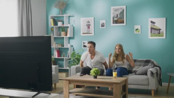 Fiatal pár néz foci a tévében egy kanapé egy hangulatos nappaliban