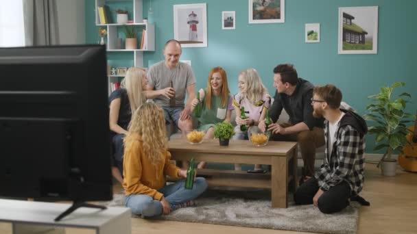 Junge Freunde klinken Gläser nach ihrem Teamsieg beim Fußballschauen im Fernsehen