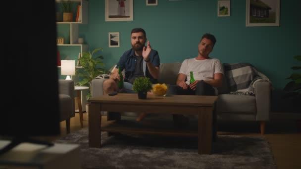 Zwei junge Männer beobachten Spiel auf TV und Wut diskutieren Spiel und verlieren Team