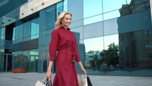 Atraktivní dívka procházka poblíž nákupního centra s plným nákupem nákupních tašek