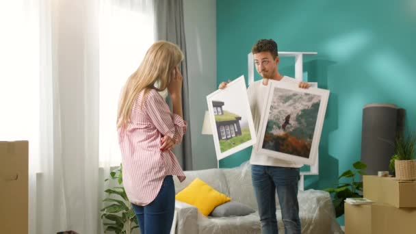 Young couple chooses wall paintings in a new apartment