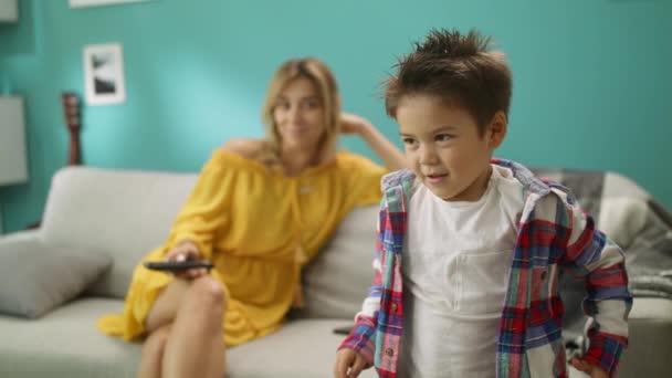 Porträt eines Jungen, der mit seiner Mutter emotional Zeichentrickfilme guckt