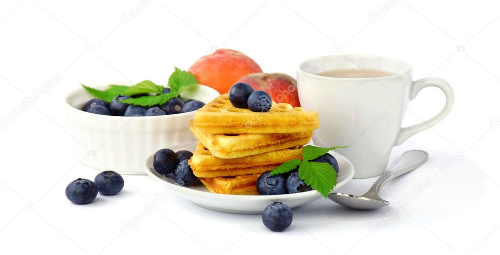 belgian waffles with blueberries and peaches and powdered sugar.  A cup of hot coffee. Breakfast. Isolated on white.