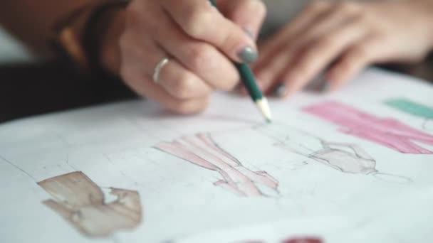designer of clothes makes an outline of clothes with a felt-tip pen. female hands closeup