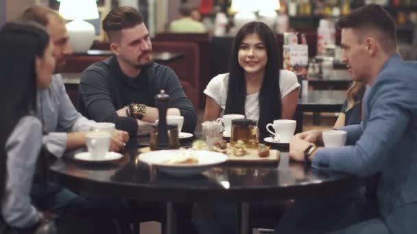 přátelé smát a bavit sedět u stolu v restauraci. Společnost přátel spolu tráví čas a těší socializace.