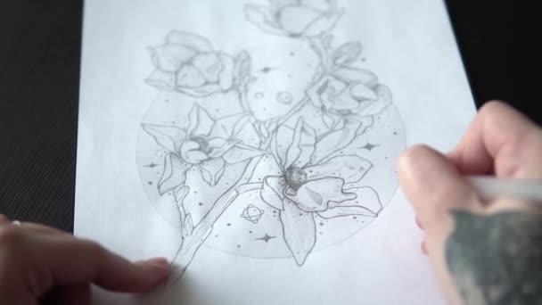 tattoo master makes a sketch of tattoo on paper