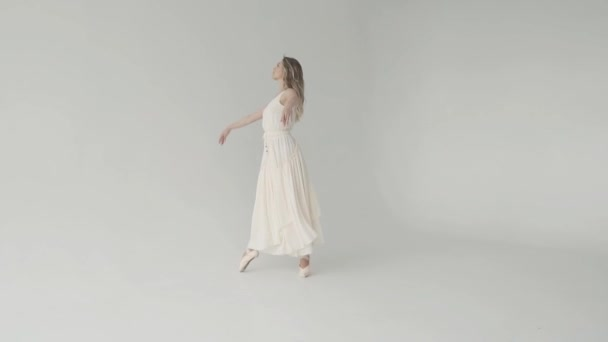concept of freshness, youth and beauty. ballerina in white waving dress and pointes beautifully dancing on white background. slow motion