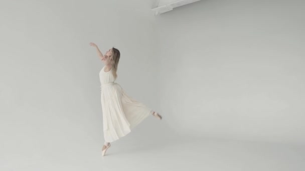 elegant and graceful ballerina dancing in a white flying dress and pointe shoes on a white background. slow motion