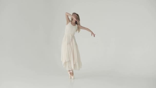 A graceful ballerina makes smooth movements with her hands. a ballet dancer in a long waving dress and pointe shoes