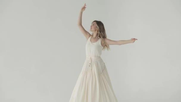 a vonzó lány táncol egy fehér ruhás világoson.