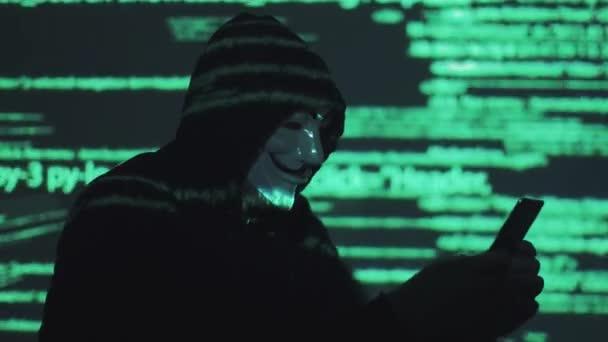 un rapinatore sullo sfondo dellesecuzione del codice programma tiene uno smartphone nelle sue mani. hacker ruba altri dati di popoli mediante un telefono cellulare