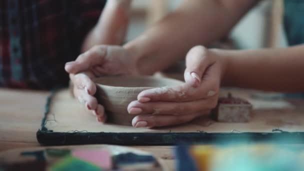 dívka modeluje hliněné desky. okupace na ruční modelování z hlíny. ženské ruce detail.