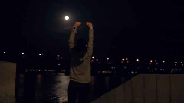 concept of joy of victory and achievement. the girl happily raises his hands up. portrait of the athlete at the end of training on background the night city.