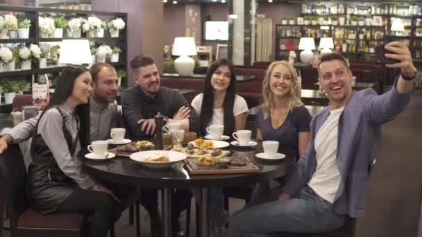 a large group of friends makes a selfie sitting at a table in a cafe or restaurant.