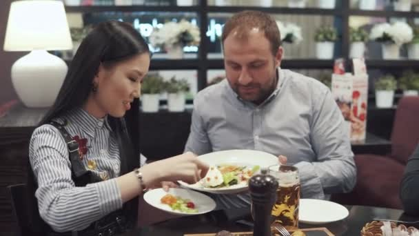 company of friends in a cafe or restaurant. a young man puts a salad on a plate to his girlfriend