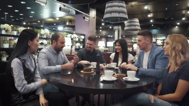velkou skupinou přátel mluví a Bavíte se spolu sedí u stolu v kavárně nebo v restauraci