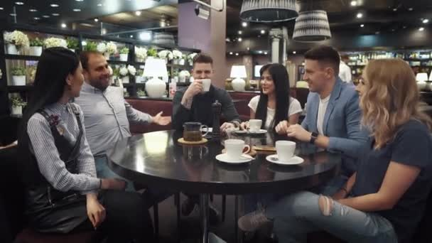 large group of friends talking and having fun together sitting at a table in a cafe or restaurant