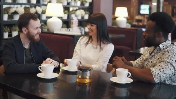 multi-ethnic company of friends. friends drink tea and have fun. a company of three friends in a restaurant and a cafe. two young men and a girl are sitting at a table in a cozy restaurant.